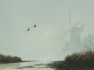 A windmill stands on the banks of a river estuary in the morning mist. Windmills were once a common sight but are more of a rare sight today. ......